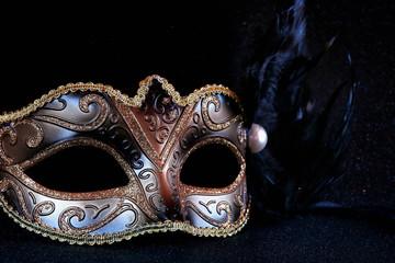 black venetian mask on glitter background