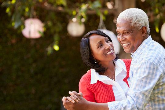 Senior black couple dancing in their backyard, close up