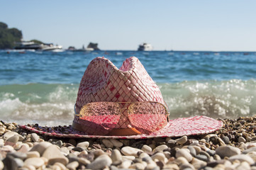 Women's straw beach hat (sunhat) with sunglasses lies on the pebble beach, surrounded by round stones on a background of blue sea with an island, waves, boats and yachts. Idea for summer beach holiday