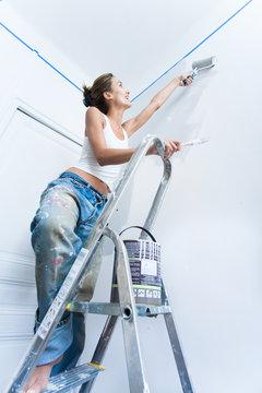 femme souriant debout sur un escabeau qui peint un mur