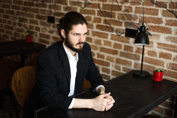 young bearded man in a jacket and white shirt sits at a table in cafe
