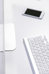White Office Desk with Computer Keyboard and Smartphone