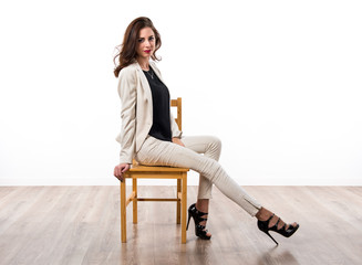 Beautiful brunette girl sitting on wooden chair