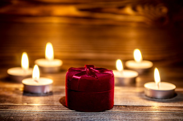 Red box with a ring on the background of burning small candle.