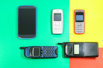 Old mobile phones used and outdated on colorful pop style background top view image - Concept of technological development in communications devices