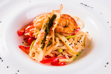 Italian pasta with whole shrimp and slices of bell pepper in a white plate on a light  background