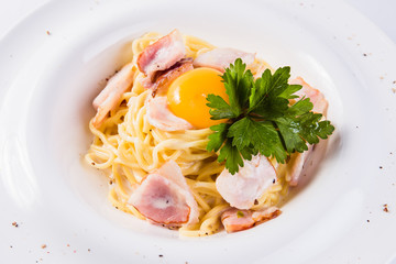 pasta with bacon and egg yolk on a white plate on a light background