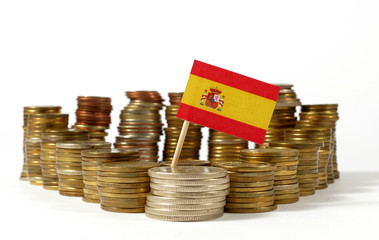 Spain flag waving with stack of money coins