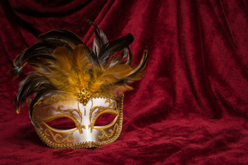 Brown golden venetian carnival mask seen from the front on a draped red velvet theater curtain