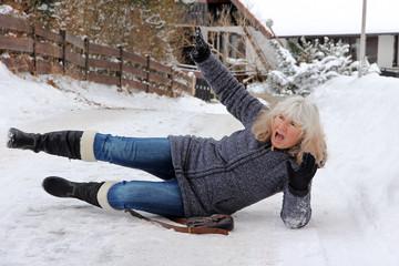 Unfallgefahr im Winter - Eine Frau ist auf einer schneeglatten Straße ausgerutscht