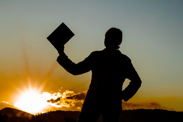 silhouette of a woman holding up a book