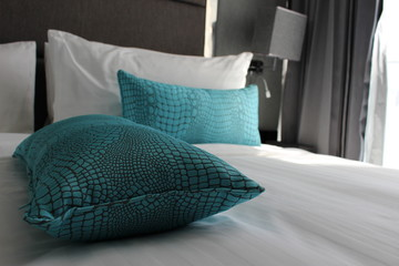Comfy hotel bed with turquoise cushions