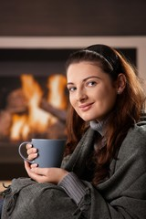Drinking tea in front of fireplace