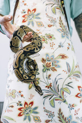 Man dressed in apron holding snake
