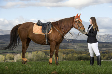 Woman posing with brown horse
