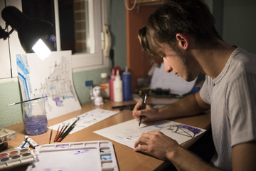 Young thoughtful man drawing