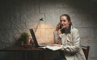 Mature woman talking phone at her workplace