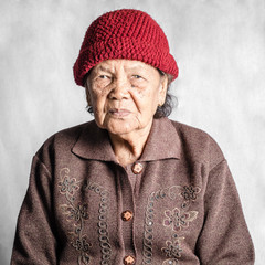 Portrait of a senior woman with vintage costume. Isolated on gre