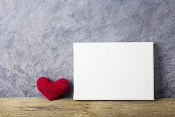 Love concepts of red heart and blank canvas frame on wood table for valentines day and wedding