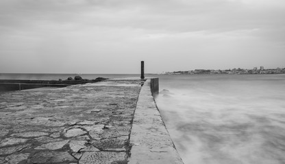 Jetty with storm dramatic clouds in background. Estoril in Portugal