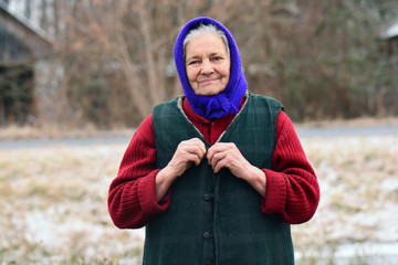 Portrait of old woman in blue headscarf in village