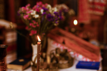 Single candle with dripping wax and blurring lights of many candles in two candlesticks at background.