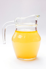 Glass jug of chicken broth isolated on white background