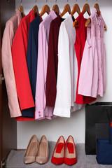 Elegant female clothes in wardrobe, closeup