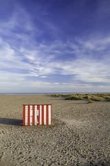 Secluded vacation getaway striped beach hut. Ideal postcard image with copy space.