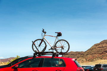 Car is transporting bicycle on the roof.