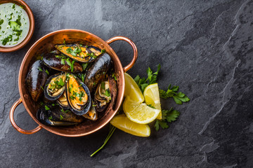 Photo sur Plexiglas Coquillage Mussels in copper bowl, lemon, herbs sauce and white wine.