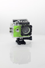 Isolated green action cam against a white background casting a reflection