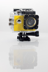 Isolated yellow action cam against a white background casting a reflection