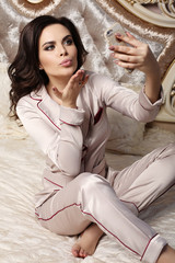 gorgeous woman with dark hair in cozy pajamas lying in bed