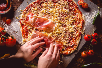 Girl is preparing homemade pizza on wooden table