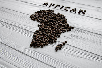 Aluminium Prints Coffee beans Map of the Africa made of roasted coffee beans laying on white wooden textured background and space for text