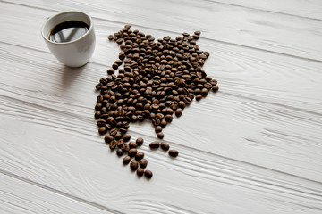 Aluminium Prints Coffee beans Map of theNorthern America made of roasted coffee beans laying on white wooden textured background with cup of coffee and space for text