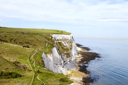 Coastal walking path overlooking the English Channel and white cliffs of Dover, south east England, on a sunny summer day .