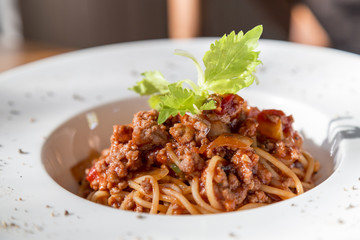 spaghetti tomato sauce with beef and pork in white deep plate