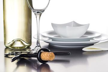 Korkenzieher mit Naturkorken vor Weinflasche, Glas und Geschirr