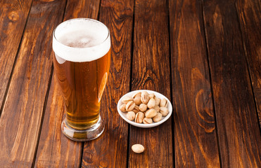 galss of light cold frothy beer, nuts old wooden table