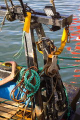 An array of deck gear on a small trawler including ropes chains stanchions lights and pulleys