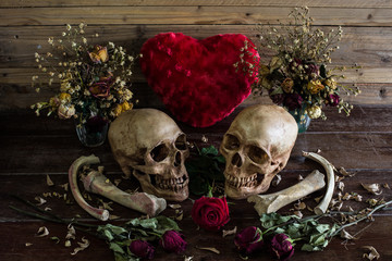Two Skulls with bone and dry flowers in dim valentines night