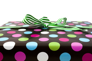 Polka dot wrapped present with green striped bow. Copy space above. Horizontal.
