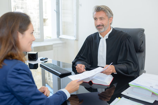 lawyer receiving contract from client in courthouse office