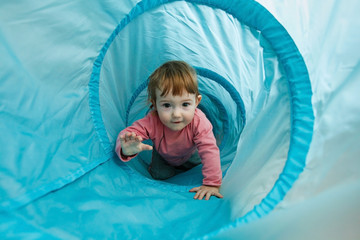 Small toddler playing in a tunnel tube