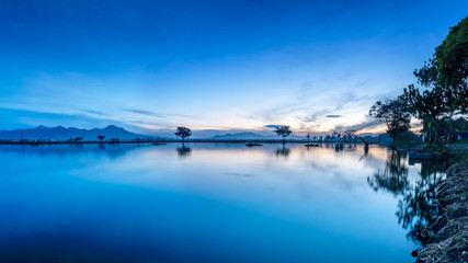 Silhouette of lonely tree in the middle of large pond or lake. Also contain mountain and the reflection in the horizon.  This photo captured at dawn, near sunrise, with beautiful blue sky,  captured i