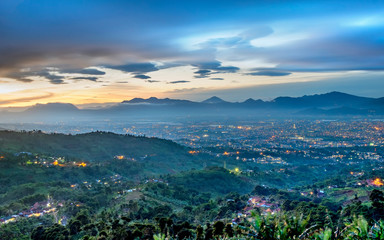 Hills and beautiful city light at night, seen faraway from top of the hilll, also showing shadow of mountain in the background, captured in Bandung, Indonesia