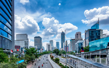 Beautiful skyline of Jakarta, Indonesia. Showing modern skyscraper buildings and beautiful blue sky and white cloud at daylight and big road with moderate traffic. Captured in Jend. Sudirman Street. Papier Peint