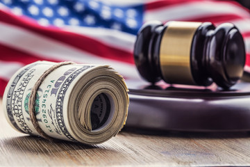 Judge's hammer gavel. Justice dollars banknotes and usa flag in the background. Court gavel and rolled banknotes. Still life of a bribery, corruption in the US judicial system.